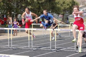 Rhett Landon soars down the track in the high hurdles race. (Photo by RANDY PARKS)