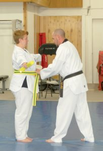 Josh Ward (R), the new owner and lead instructor at Martial Arts America, presents a student with the new belt that she earned. (Photo by SAMANTHA WHITE)