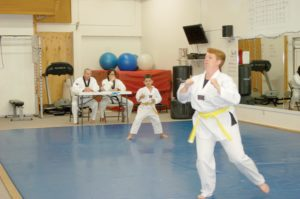 Instructors Josh Ward (L) and Evan Franulovich (R) observe students as they test for a higher belt classification.